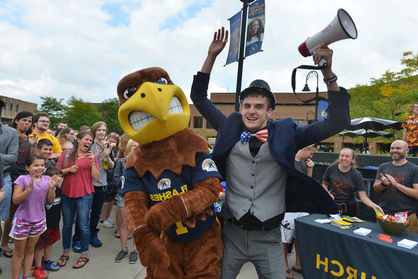 A Kent State student posing f要么 a picture with the mascot.
