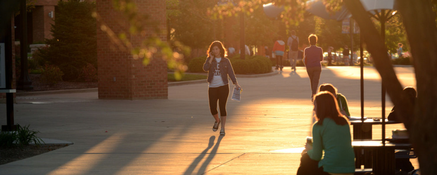 A student walks through the Risman Plaza on a warm fall evening.
