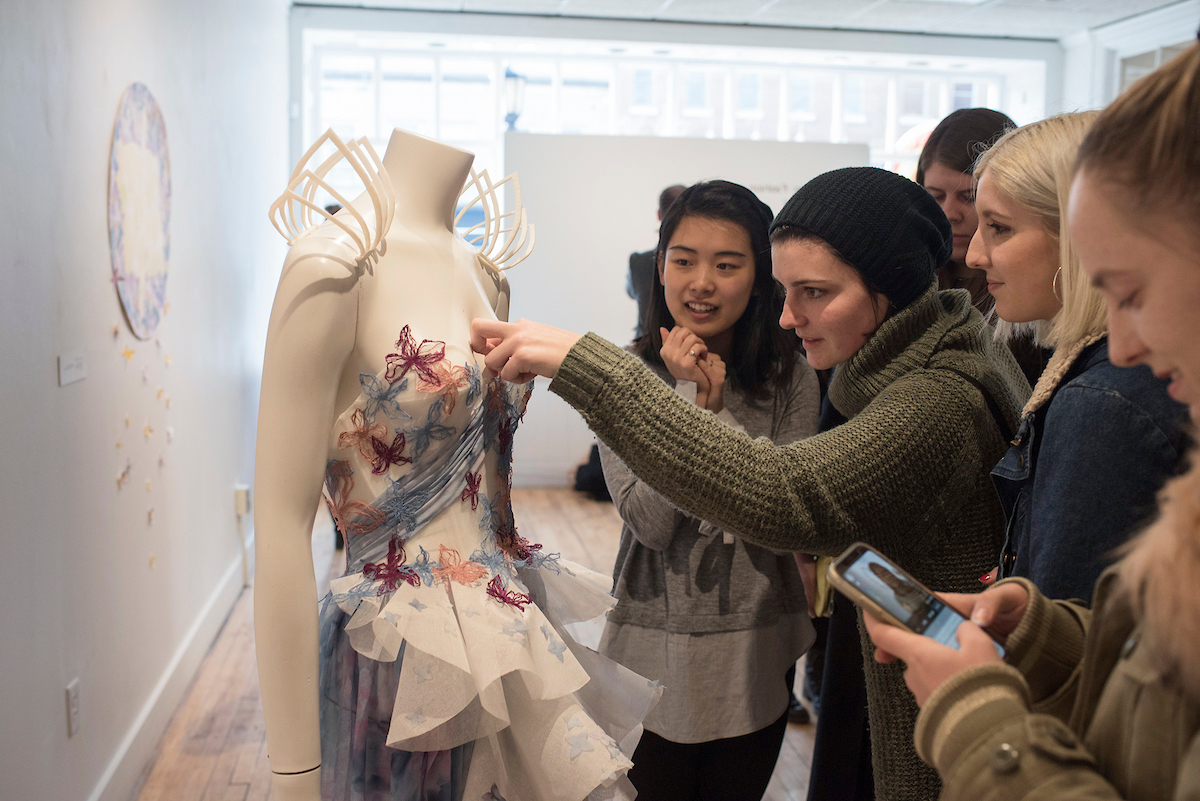 A group of students make adjustments to a dress.