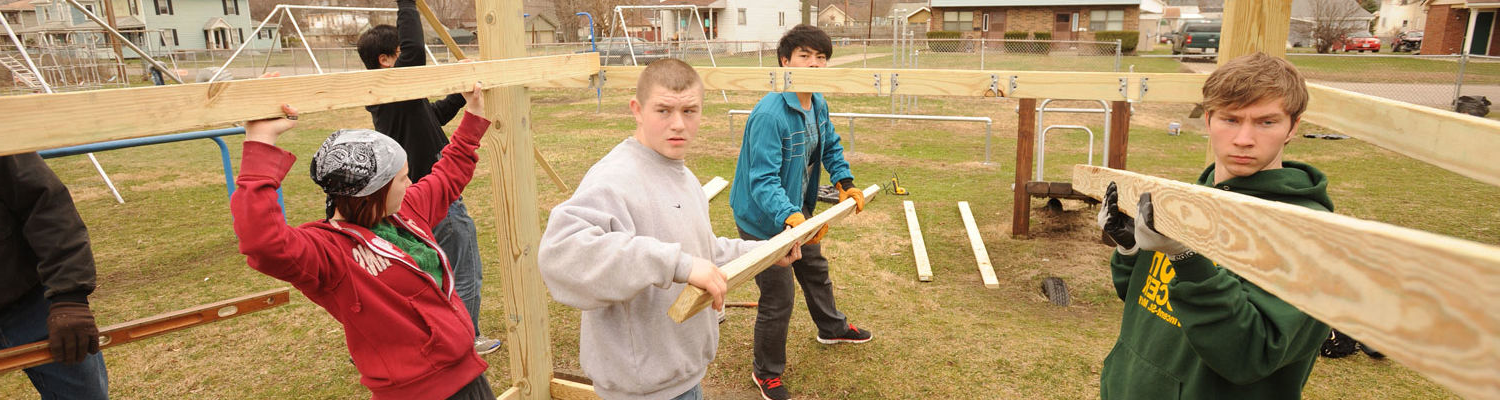 Students from the 肯特校园 build a playhouse at a park in East Liverpool as part of an alternative spring break, in which students spend a week performing community service.