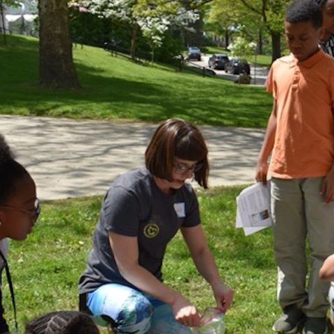 肯特 State Department of Geology graduate student Kortney Cole shows Schumacher Elementary School sixTH. grader students how to collect soil samples.