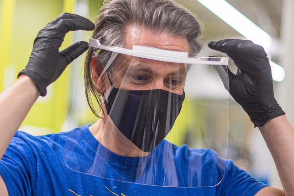 J.R. Campbell, executive director of Kent State University's 设计创新举措, tries on a face shield produced by the Kent State team.