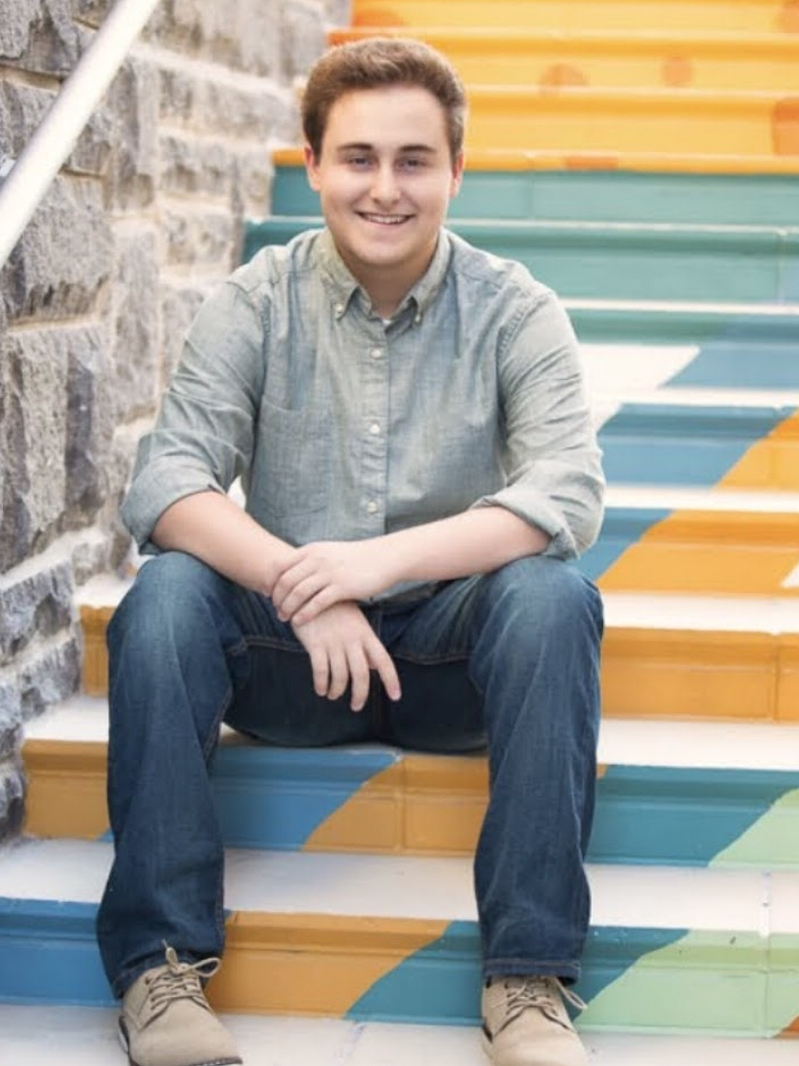 Andrew Aronoff sits on colorful steps.