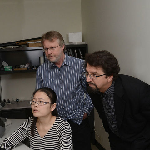 Oleg Lavrentovich, Ph.D. (second from left), works in a microscopy lab wiTH. a colleague and 肯特 State students.