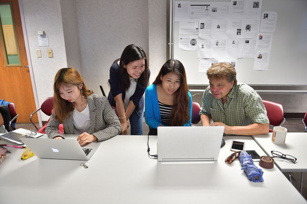 Students w要么king in a group around a computer.