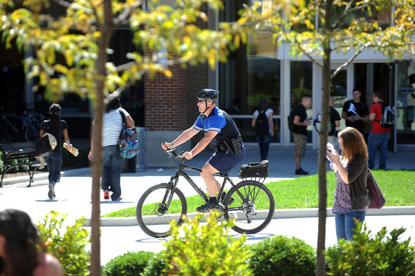 An 的ficer patrols campus on a bicycle