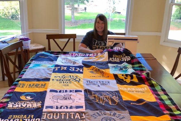 Photo of alumna with Kent State quilt
